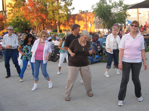 Line Dance instructor Diane Rojas, far right, dances with her students to Concert on the Promenade..jpg
