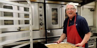 Curtis Moore, owner of Safari Crunch, removes a pan of Cherry Cheetah granola from the oven..jpg